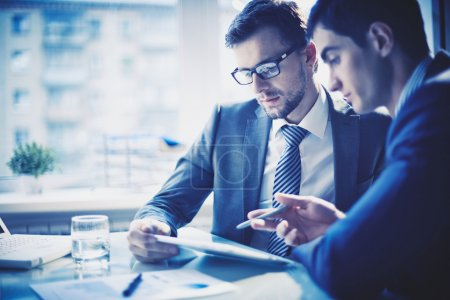 Photo for Image of two young businessmen discussing project at meeting - Royalty Free Image