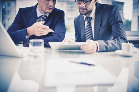 Photo for Image of two young businessmen discussing document in touchpad at meeting - Royalty Free Image
