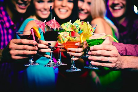 Photo for Glasses with cocktails held by happy friends at party - Royalty Free Image