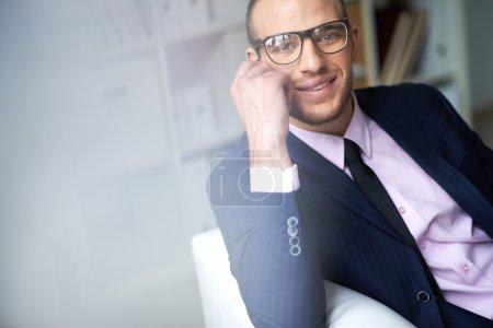 Photo pour Portrait d'homme séduisant en costume et lunettes regardant la caméra avec le sourire - image libre de droit