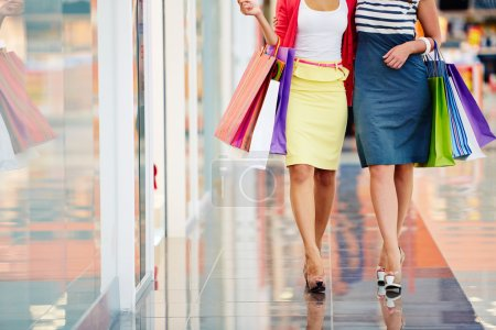 Photo for Legs of shoppers with paperbags walking down trade center - Royalty Free Image