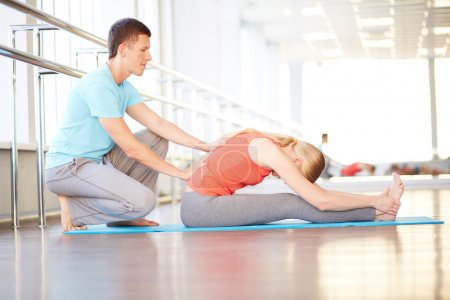 Woman doing exercise with help of her trainer