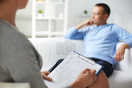 Photo for Female psychologist making notes during psychological therapy session - Royalty Free Image