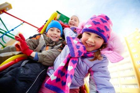 Happy friends having fun on playground in winter