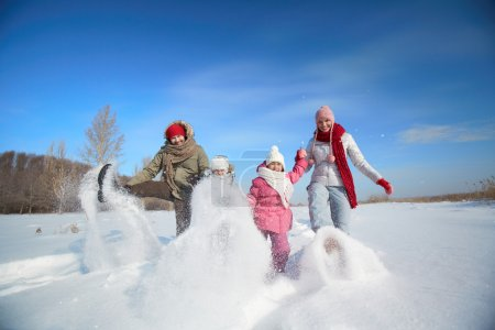Parents and their kids in winterwear having fun