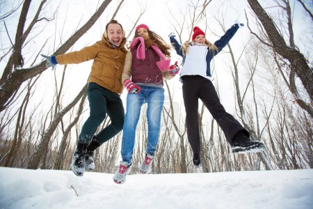 Happy friends jumping in winter