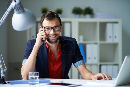 Foto de Empresario guapo hablando por teléfono y trabajando con el portátil en la oficina - Imagen libre de derechos