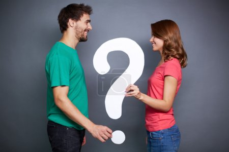 Couple holding paper question mark