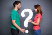 pareja sosteniendo papel de signo de interrogación