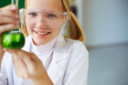 Photo for Portrait of cute schoolgirl holding tube with chemical liquid and looking at camera - Royalty Free Image