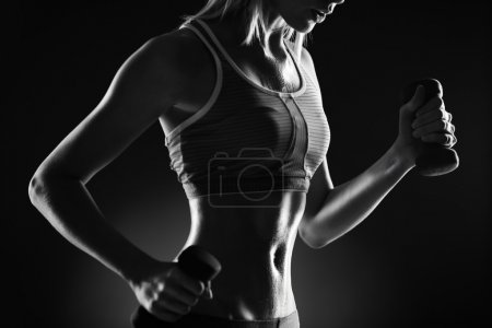Photo for Body of slim female in activewear doing exercise with dumbbells - Royalty Free Image