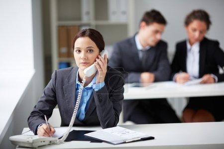 Smart businesswoman calling on phone