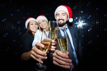 Foto de Tres socios de negocios en Santa Caps brindando con champán en discoteca - Imagen libre de derechos