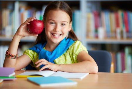Photo pour Portrait d'écolière heureux avec grosse pomme rouge en regardant la caméra dans la bibliothèque - image libre de droit