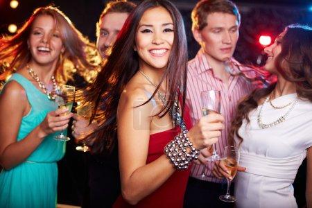 Photo pour Portrait d'un peuple joyeux avec flûtes à champagne dansant au parti en souriant à la caméra - image libre de droit