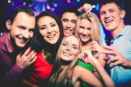 Photo pour Portrait de filles joyeux et joueurs dans des vêtements chics, regardant la caméra au parti - image libre de droit