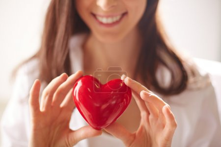 Photo for Close-up of smiling female holding red heart - Royalty Free Image