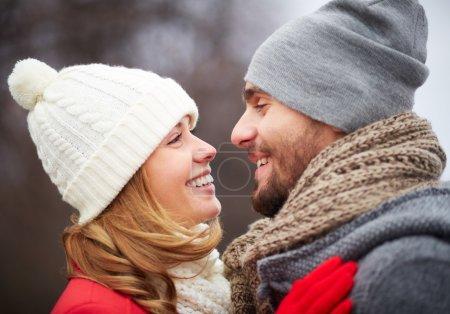 Foto de Retrato de hombre feliz con su novia en ropa abrigada mirando uno al otro - Imagen libre de derechos