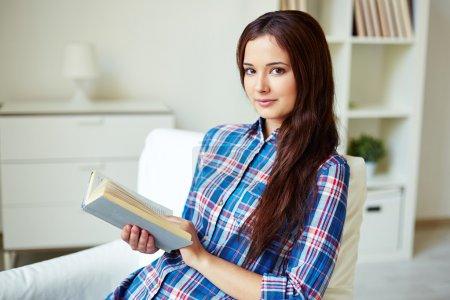 Photo pour Jolie adolescente avec livre ouvert regardant la caméra - image libre de droit