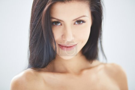 Photo for Smiling woman with dark hair looking at camera - Royalty Free Image