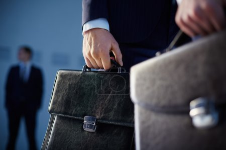 Photo for Cropped image of business partners carrying briefcases on the foreground while their colleague standing on the background - Royalty Free Image