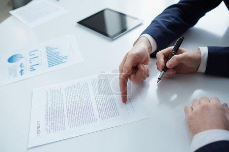 Photo pour Deux hommes d'affaires tout en signant un contrat - image libre de droit