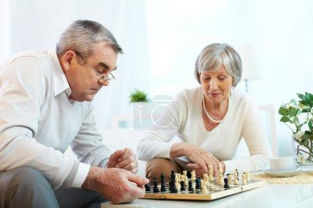 Photo pour Senior couple jouer aux échecs - image libre de droit