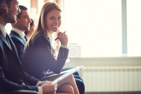 Photo for Row of business people sitting at seminar, focus on attentive young female - Royalty Free Image