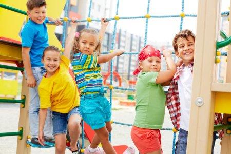 Photo pour Image de mignons amis s'amuser sur l'aire de jeux en plein air - image libre de droit