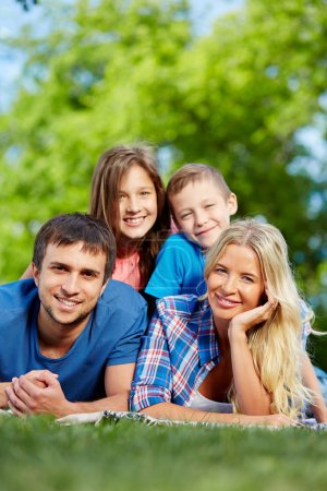 Photo for Photo of happy family of four relaxing on grass during summer rest - Royalty Free Image