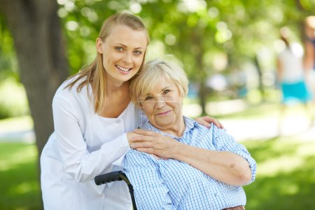 Photo for Pretty  nurse and senior patient looking at camera outside - Royalty Free Image