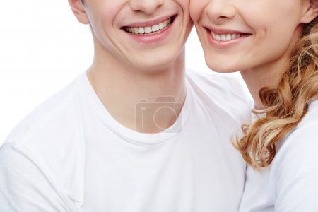 Photo for Close-up of amorous young couple in white T-shirts with toothy smiles - Royalty Free Image