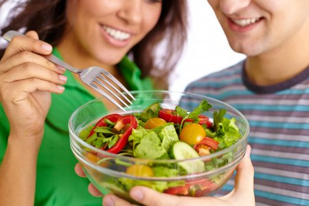 Photo for Close-up of young couple eating vegetable salad from glass bowl - Royalty Free Image