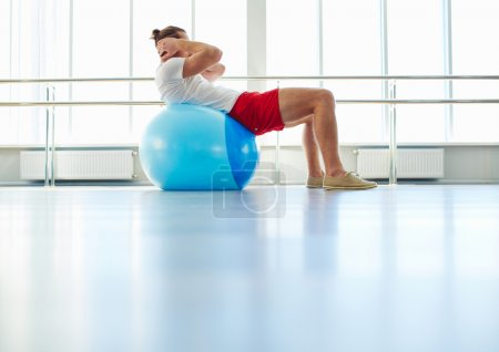 Man doing physical exercise on ball