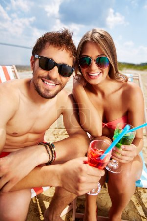 Lovers with drinks having beach party