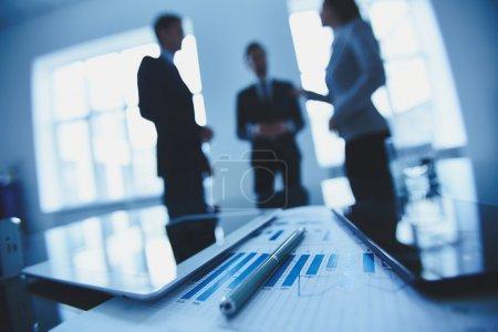 Photo pour Gros plan des documents commerciaux, des stylos et des pavés tactiles sur le lieu de travail sur le contexte des employés de bureau qui interagissent - image libre de droit