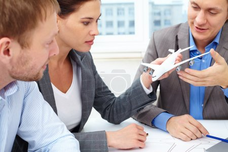 Engineers discussing small model of plane