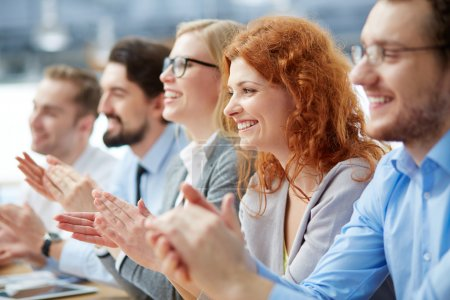 Photo for Photo of happy business people applauding at conference, focus on redhead female - Royalty Free Image