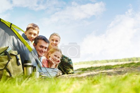 Photo for Portrait of family of travelers in tent looking at camera - Royalty Free Image