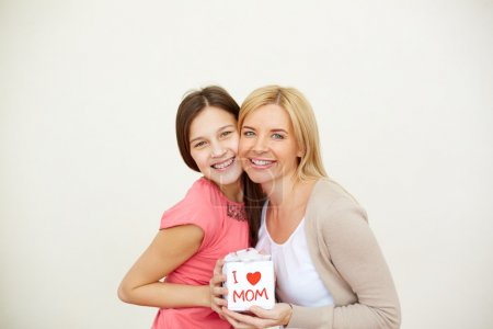 Photo for Teenage girl and her mom with small present looking at camera - Royalty Free Image