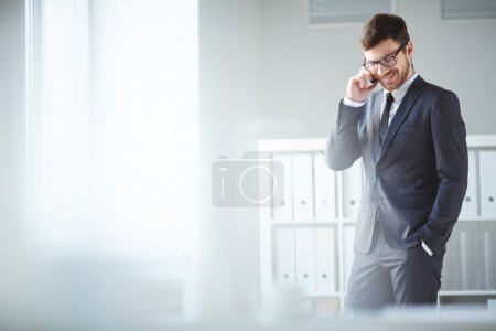 Photo for Handsome businessman in suit and eyeglasses speaking on the phone in office - Royalty Free Image