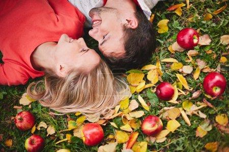 Foto de Pareja joven con manzanas maduras mirando uno al otro mientras se está acostado en el suelo - Imagen libre de derechos