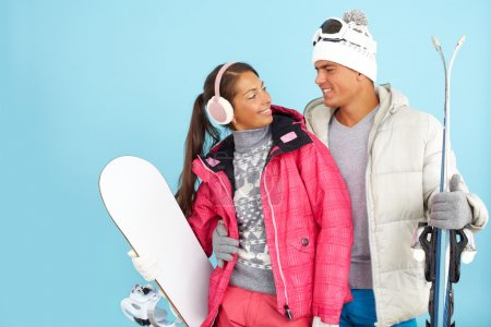 Girl and man in winterwear holding snowboard