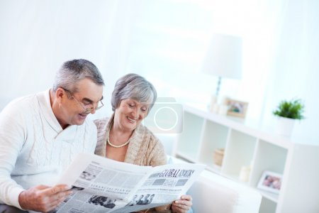 Couple of pensioners reading newspaper