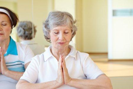 Aged women doing yoga exercise