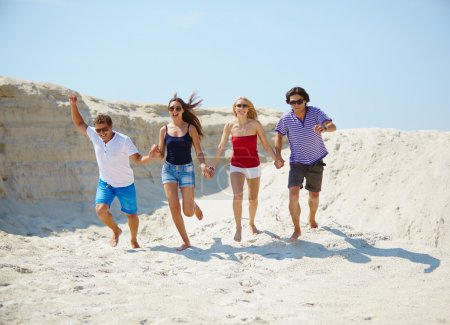 Junge Leute rennen auf dem Sand