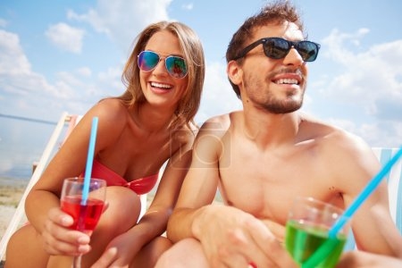 Couple with drinks on the beach