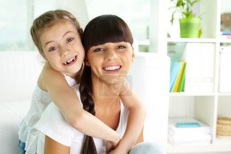 Photo for Portrait of happy girl and her mother looking at camera with smiles - Royalty Free Image