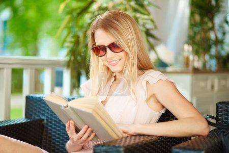 Photo pour Portrait de jolie fille en lunettes de soleil lisant un livre à loisir - image libre de droit