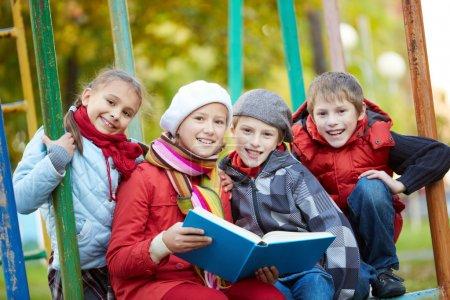 Foto de Retrato de escolares feliz leyendo un libro juntos al aire libre - Imagen libre de derechos